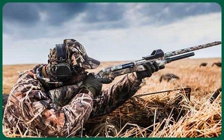 Охотник целится в коллиматорный прицел на гладкоствольном ружье